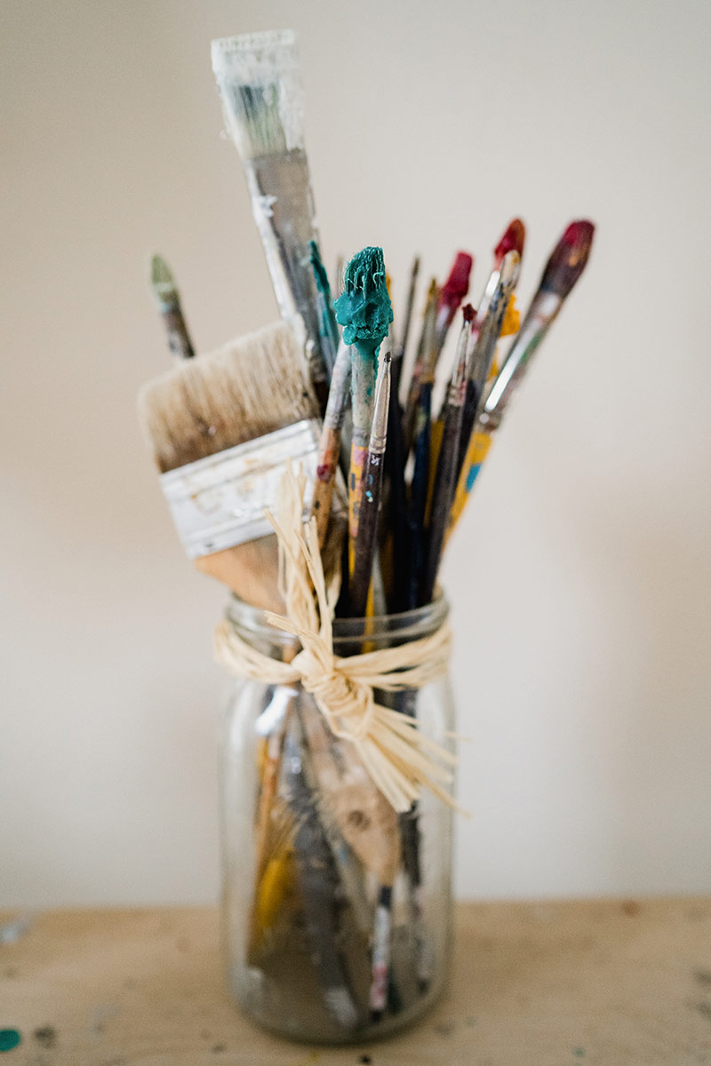 glass jar of paint brushes with blue and red paint against a white wall