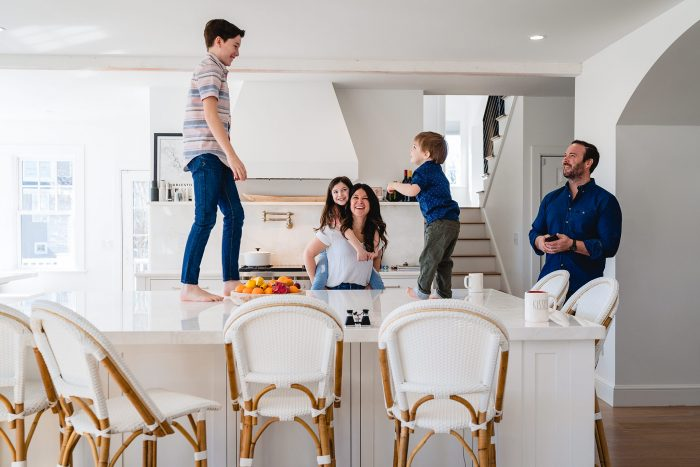 two boys dancing on counter in kitchen while mom, dad and sister laugh