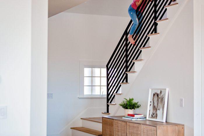 girl sliding down iron staircase