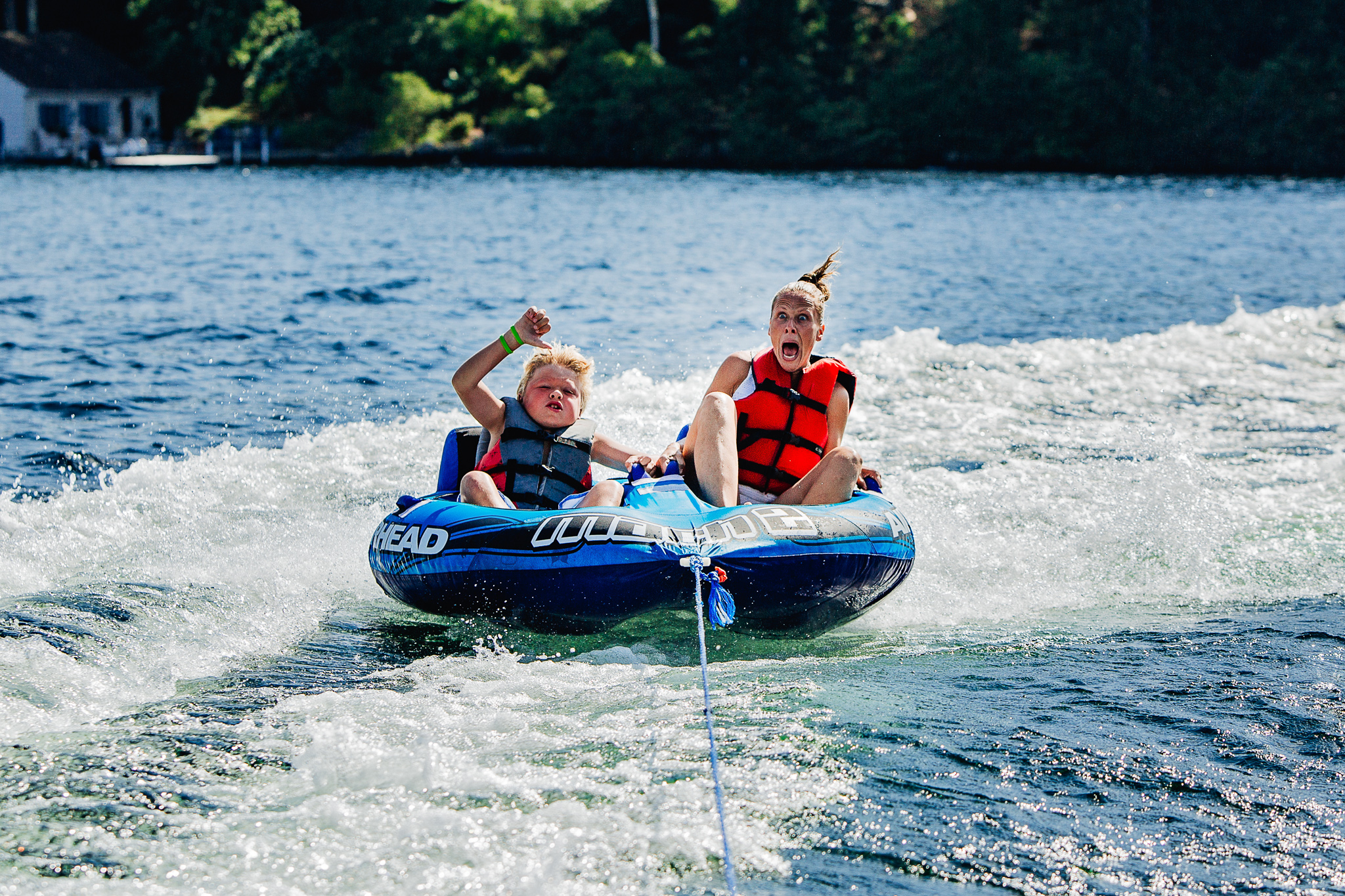 mom and son screaming while tubing on the lake