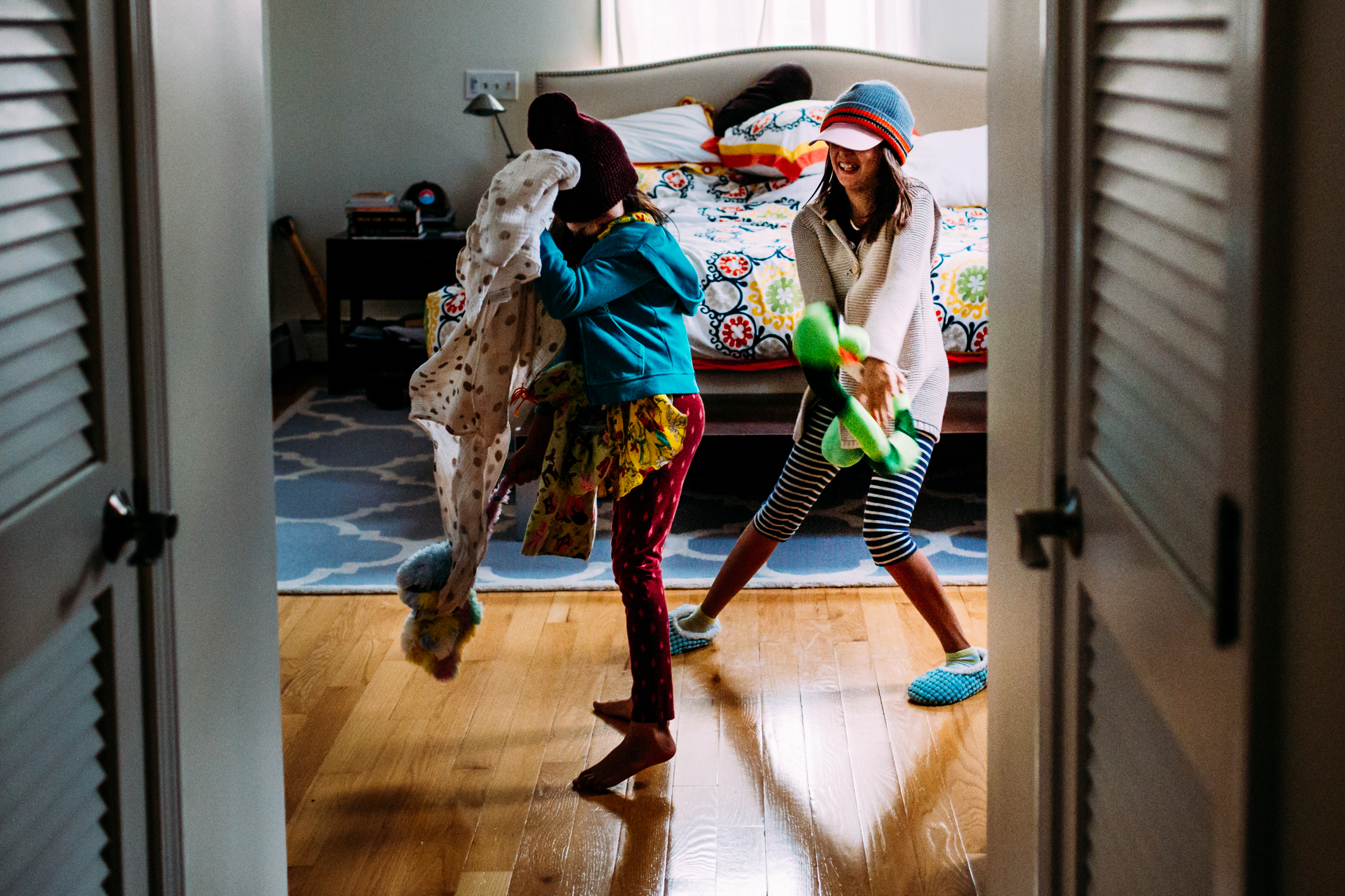 two girls throwing stuffed animals at each other