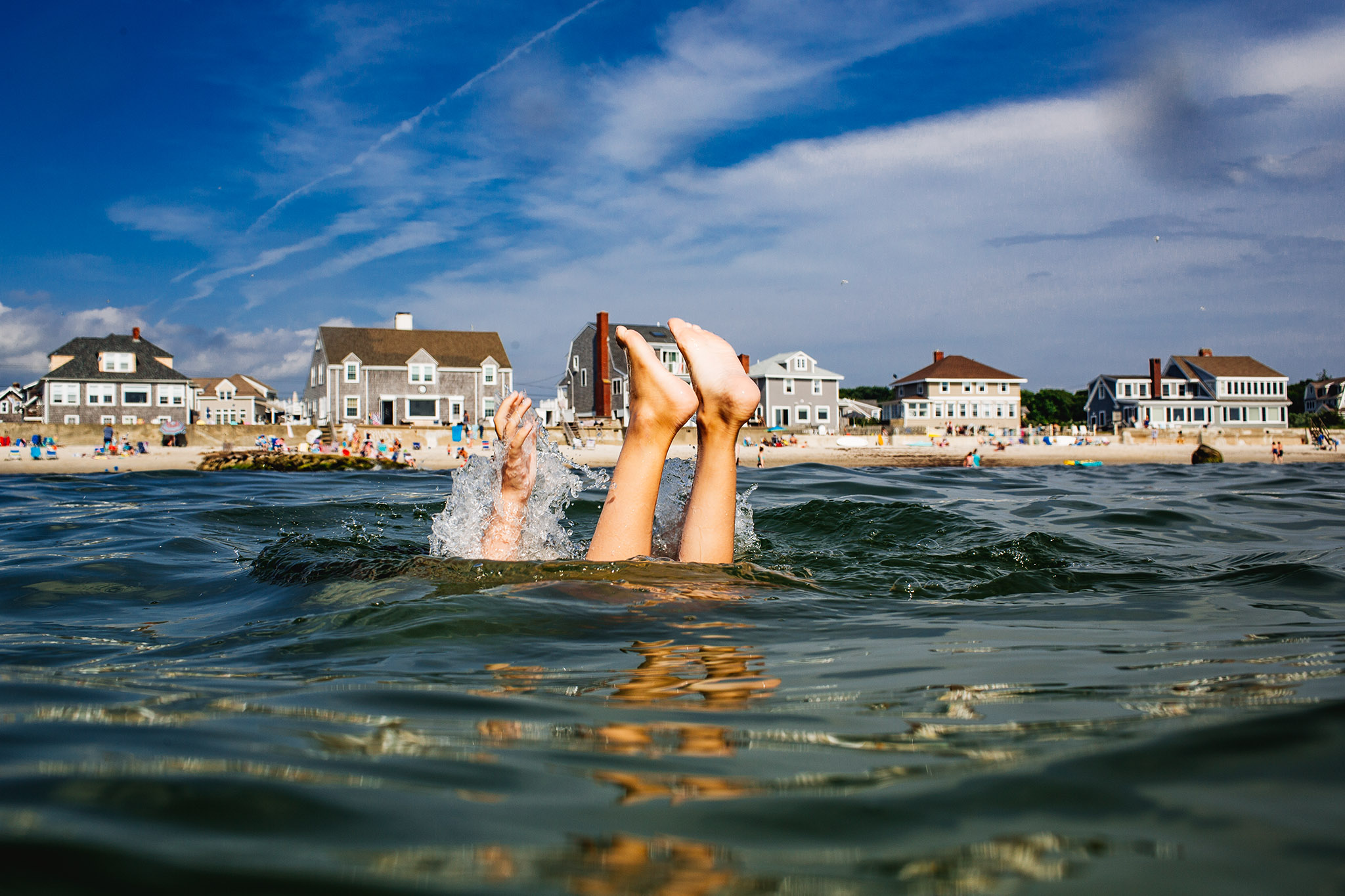 child's feet sticking up above water with beach homes in background