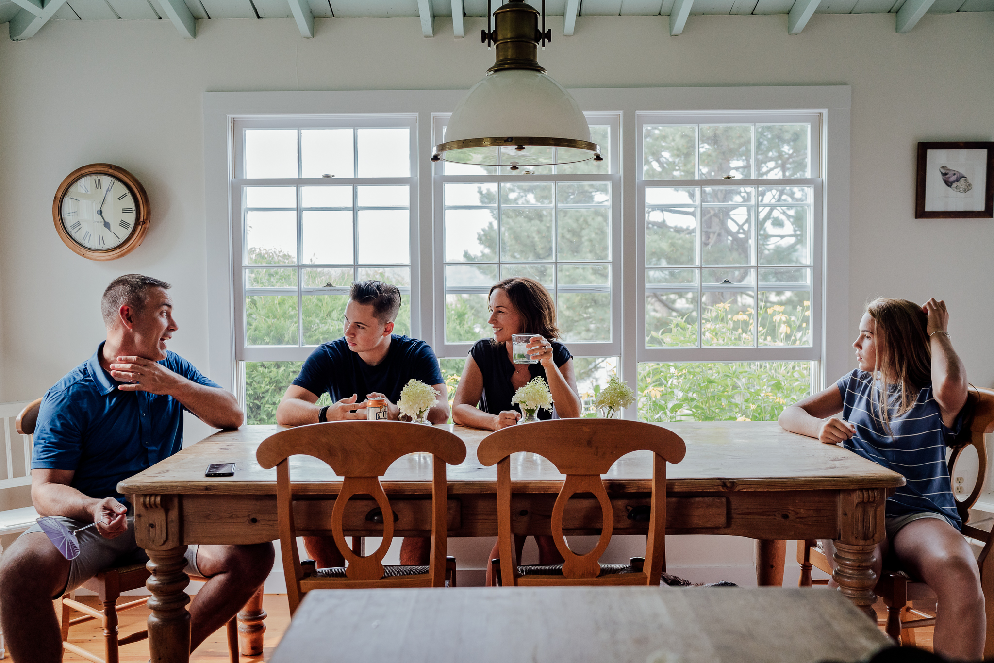 mom, dad sitting at kitchen table with teenage son and daughter