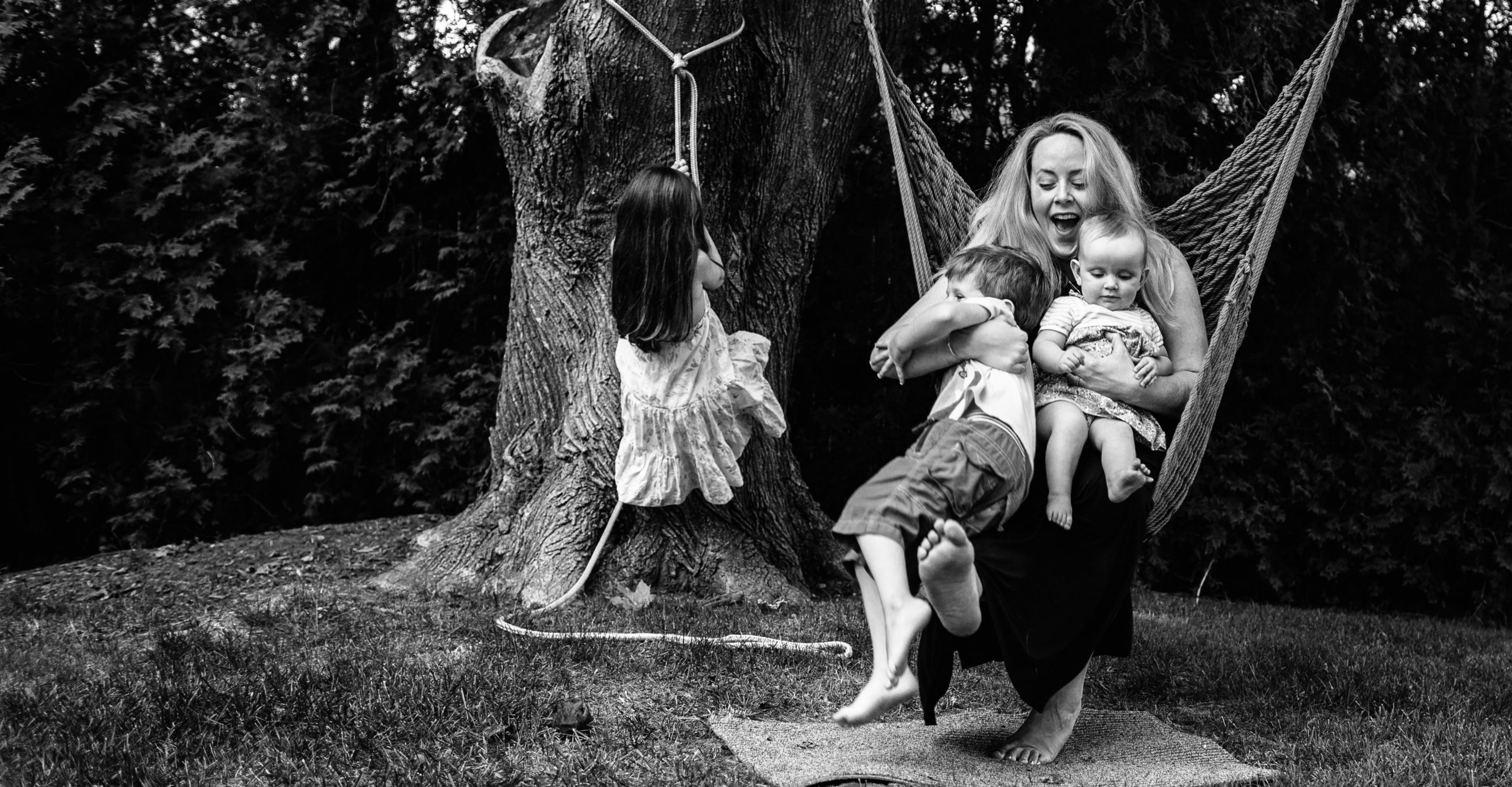 mom on rope swing with two little kids and girl climbing up tree