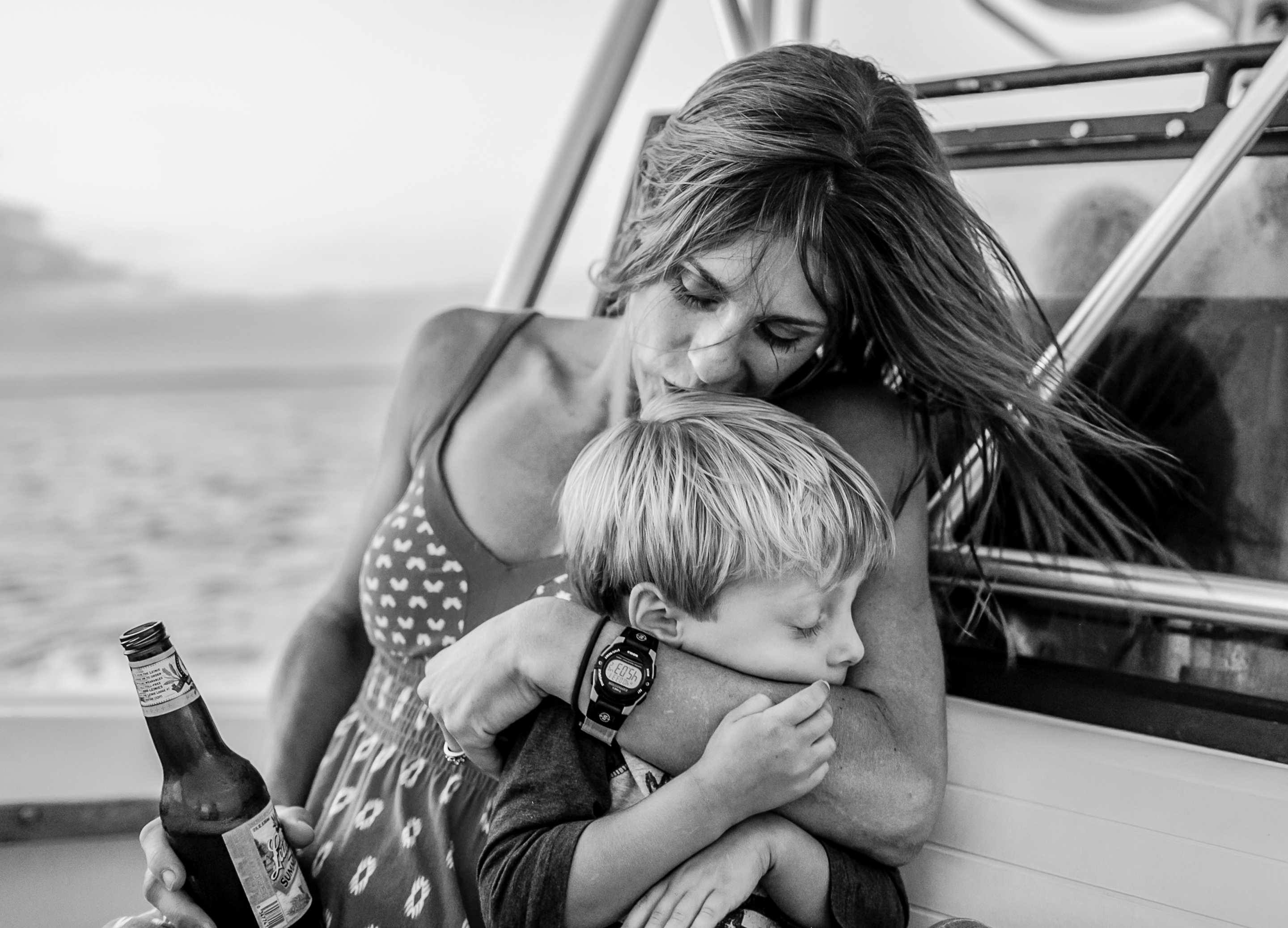 mom hugging and kissing little boy on boat