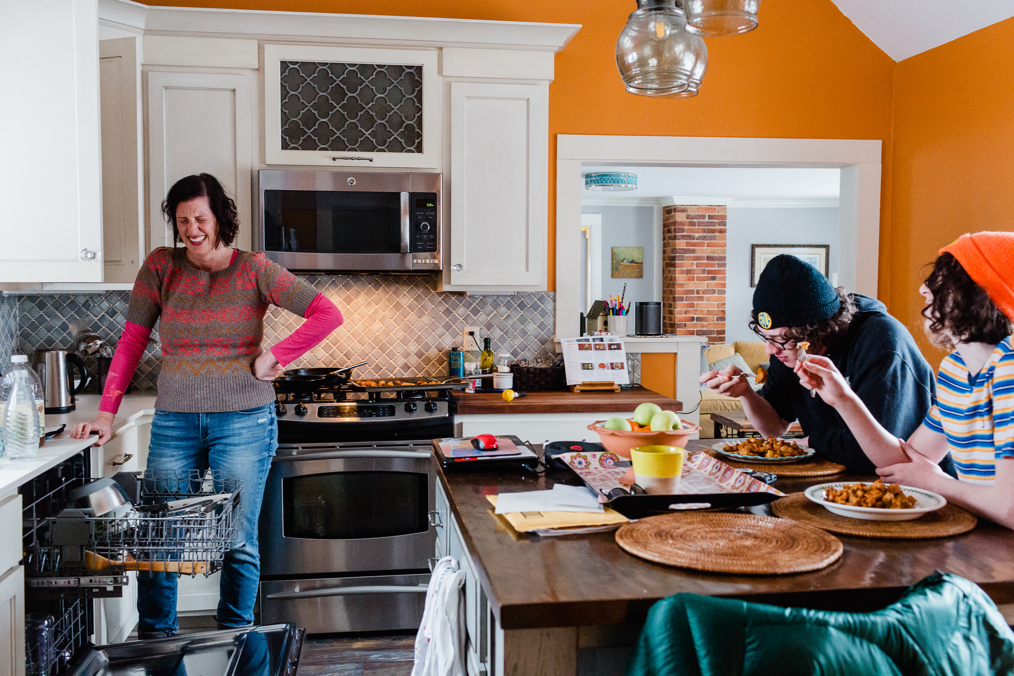 mom laughing in kitchen while two sons eat at counter