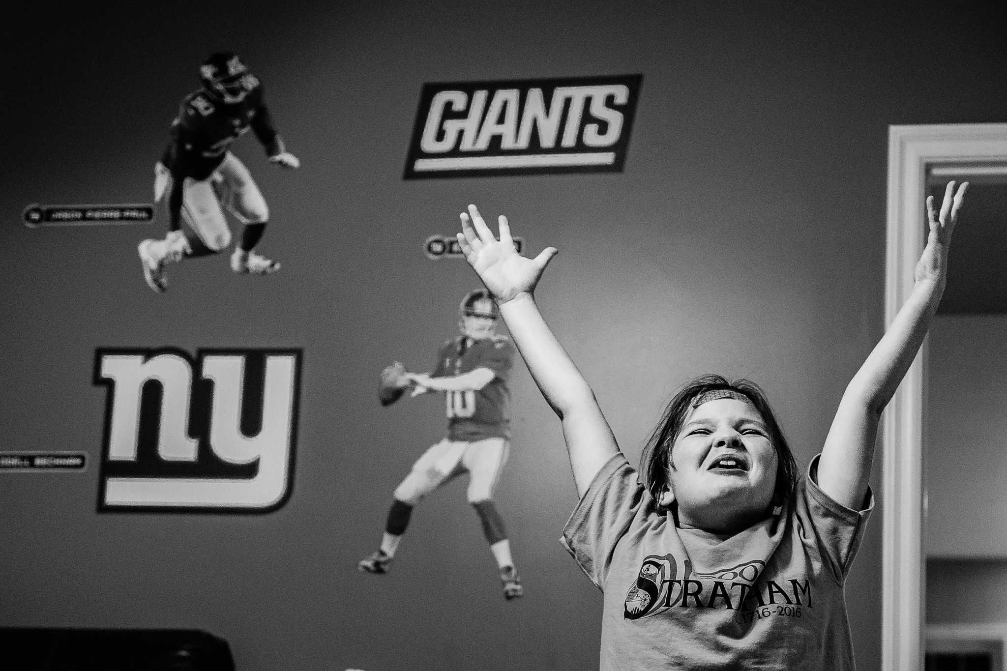 happy young girl with arms raised and giants stickers on wall