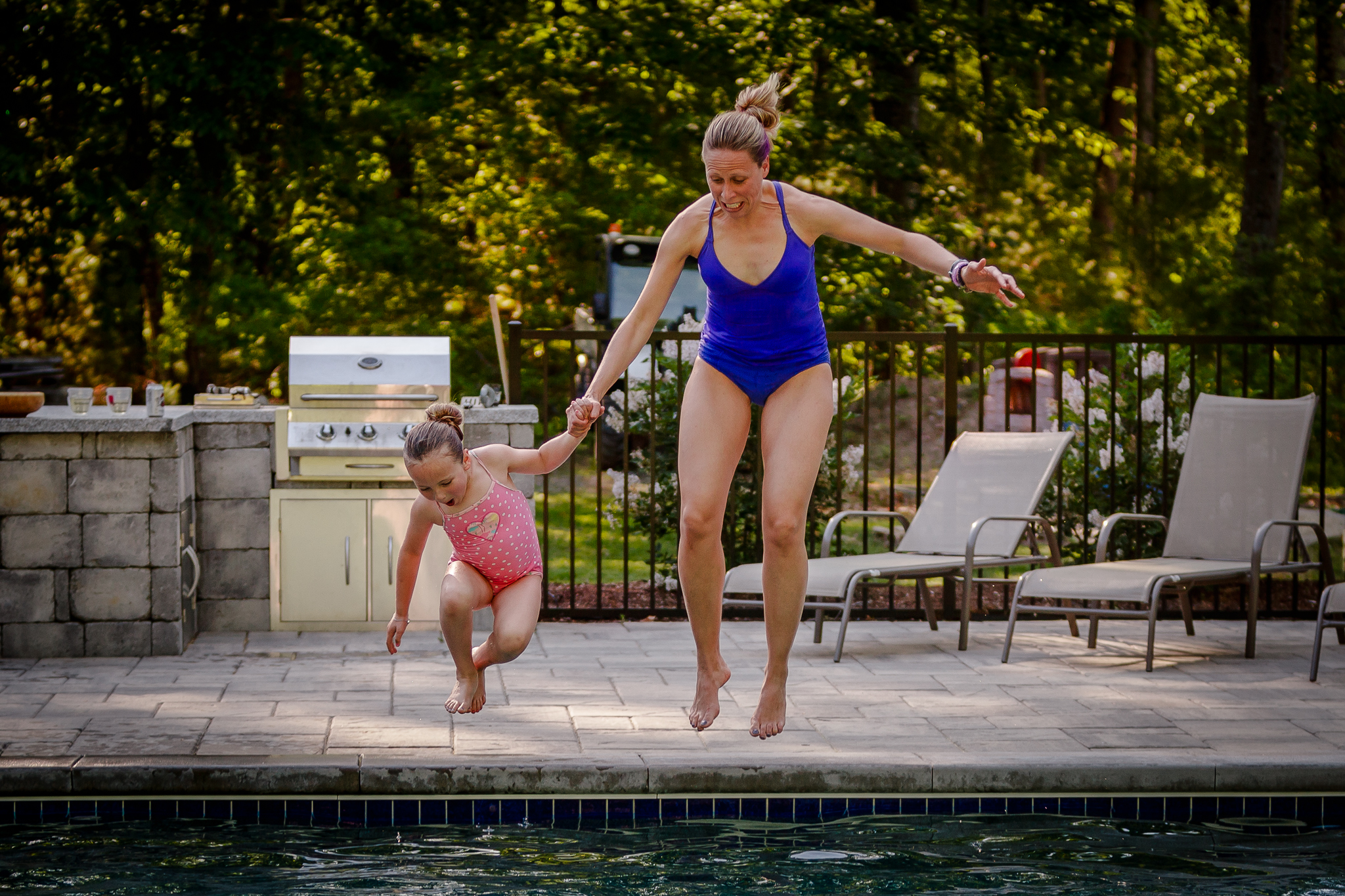 mom and daughter jumping into pool