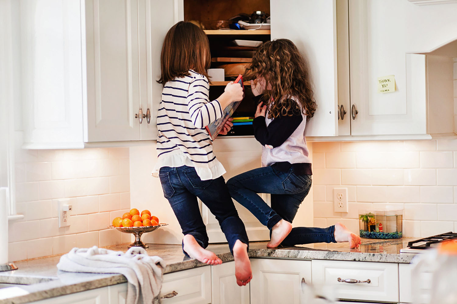 two young girls climbing on the kitchen counter