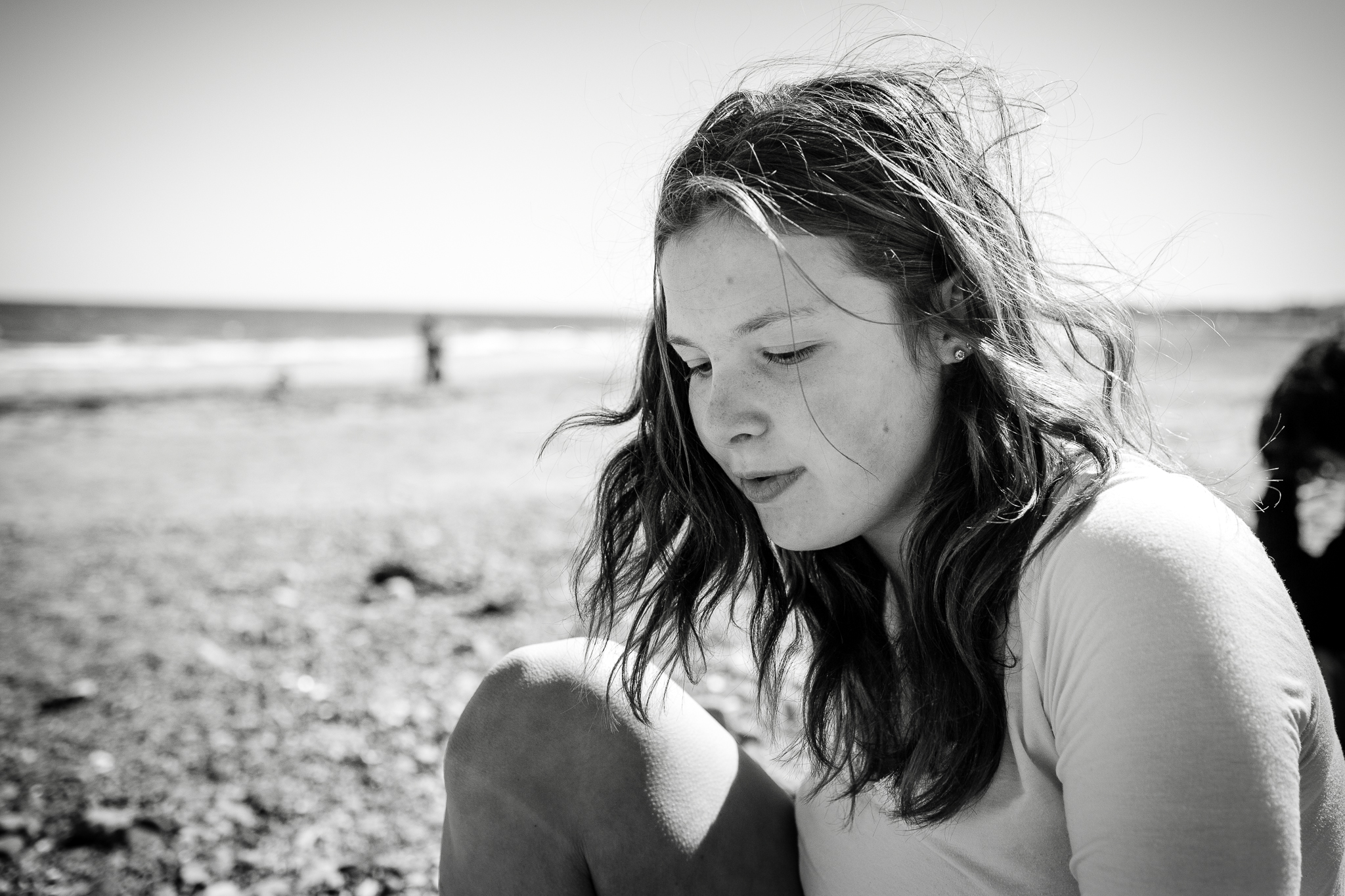 teenager sitting on beach with hair blowing
