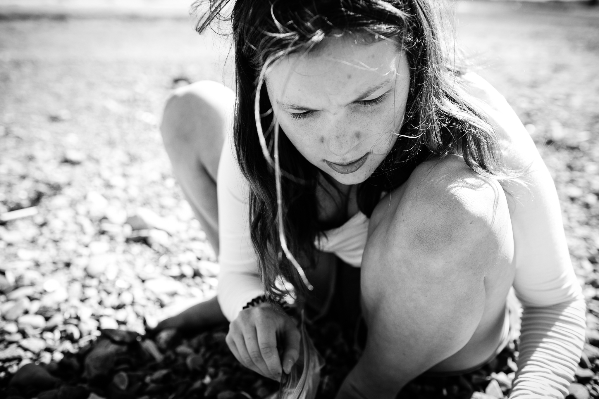 close up of teenage girl squatting on beach