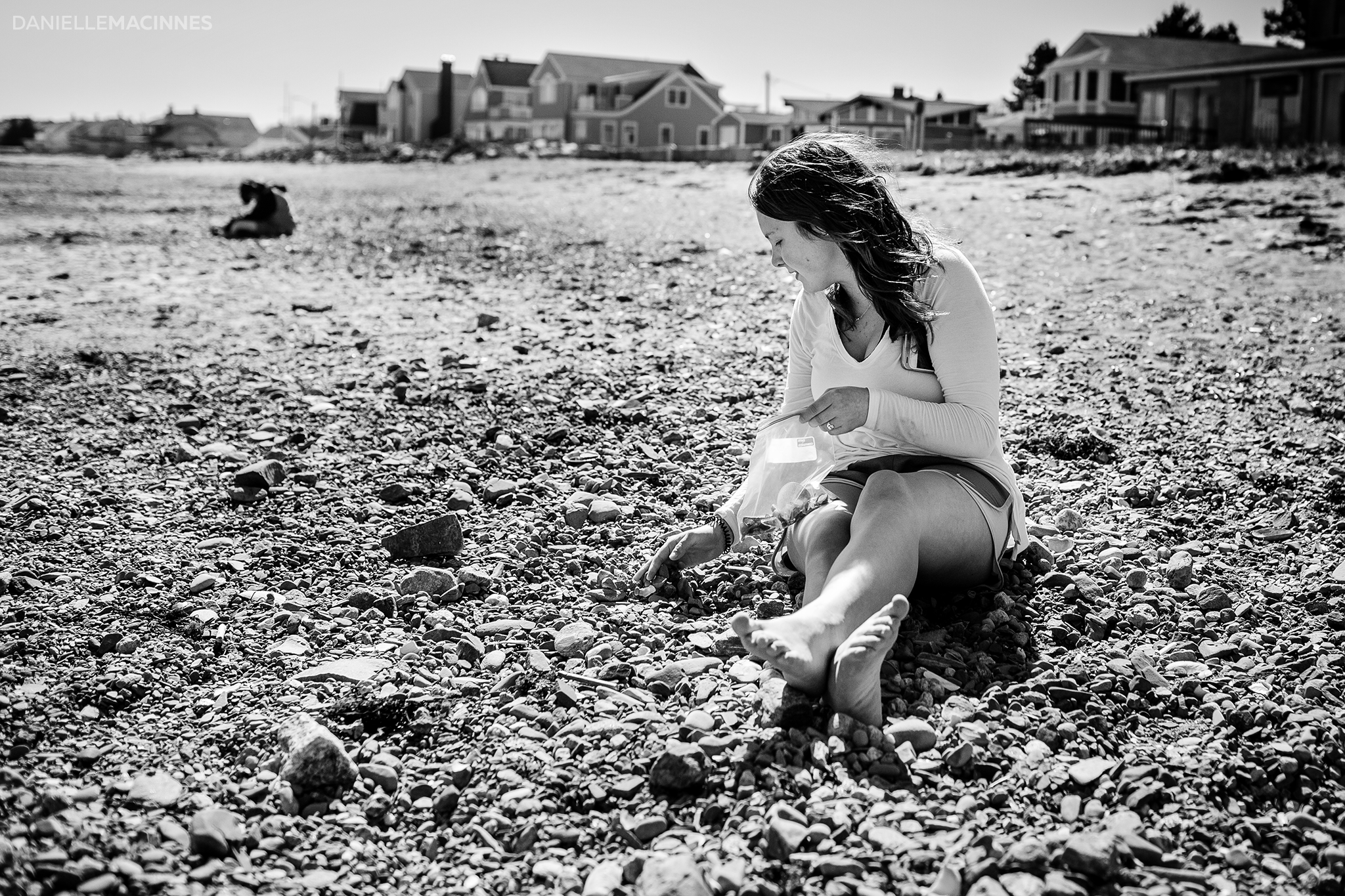 girl sitting on rocky beach looking for seaglass