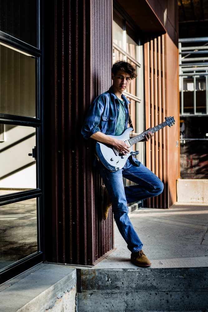 high school senior male playing guitar and leaning against a building