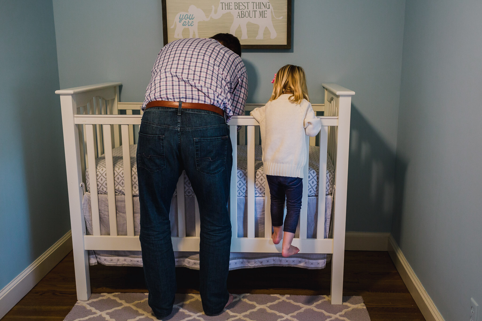young girl climbing on crib next to father