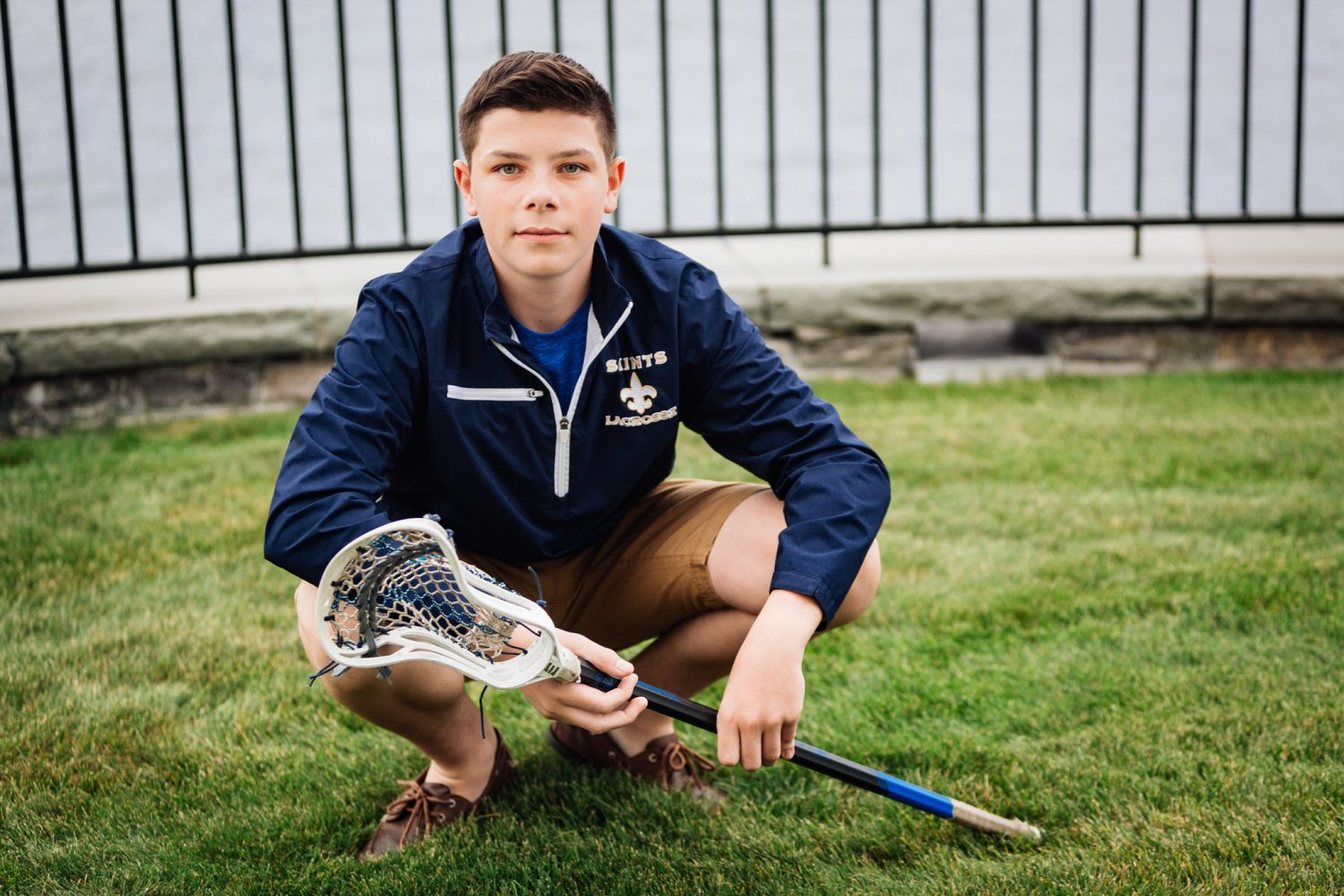 senior boy wearing blue windbreaker kneeling down holding lacrosse stick