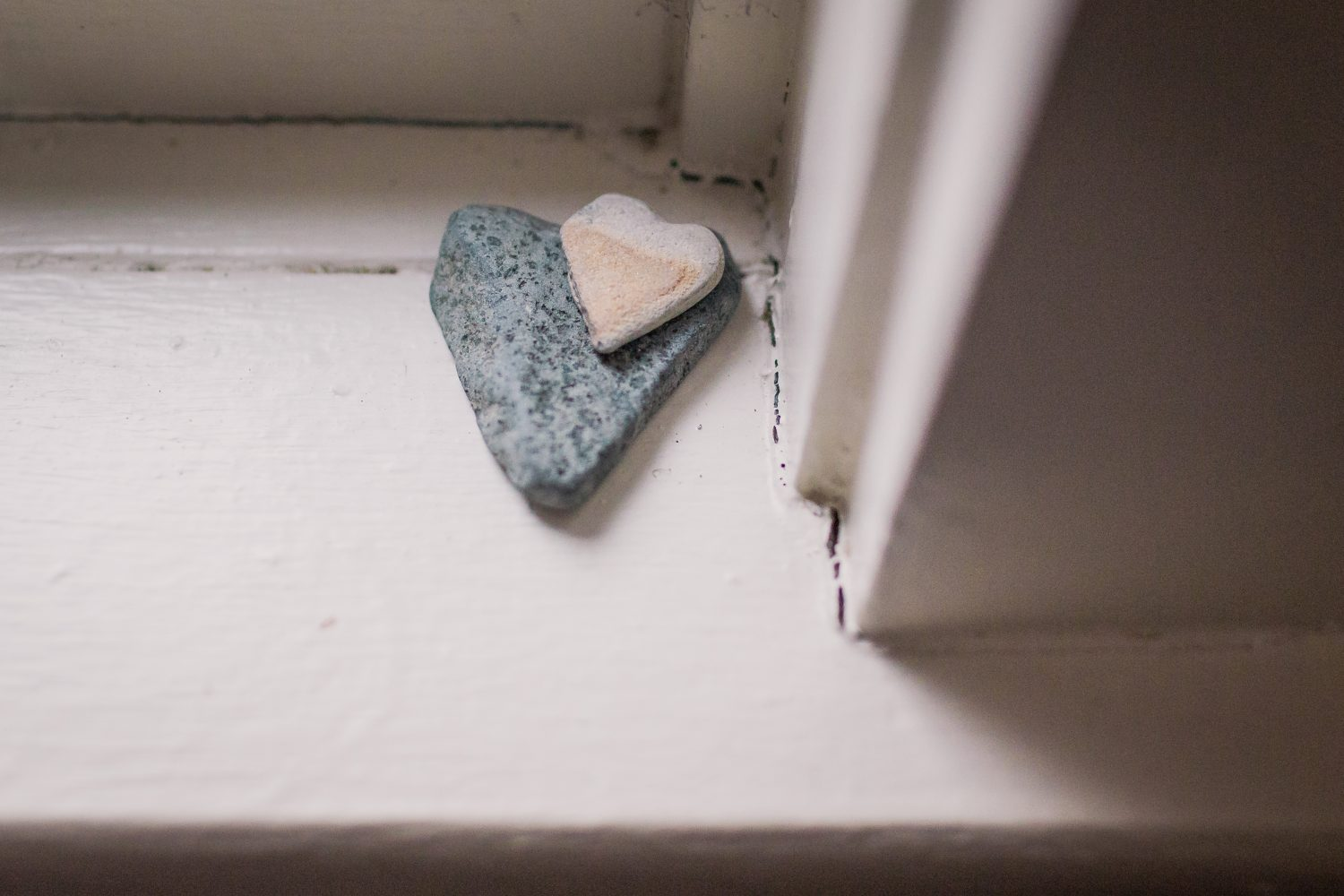 two heart shaped rocks on a window sill