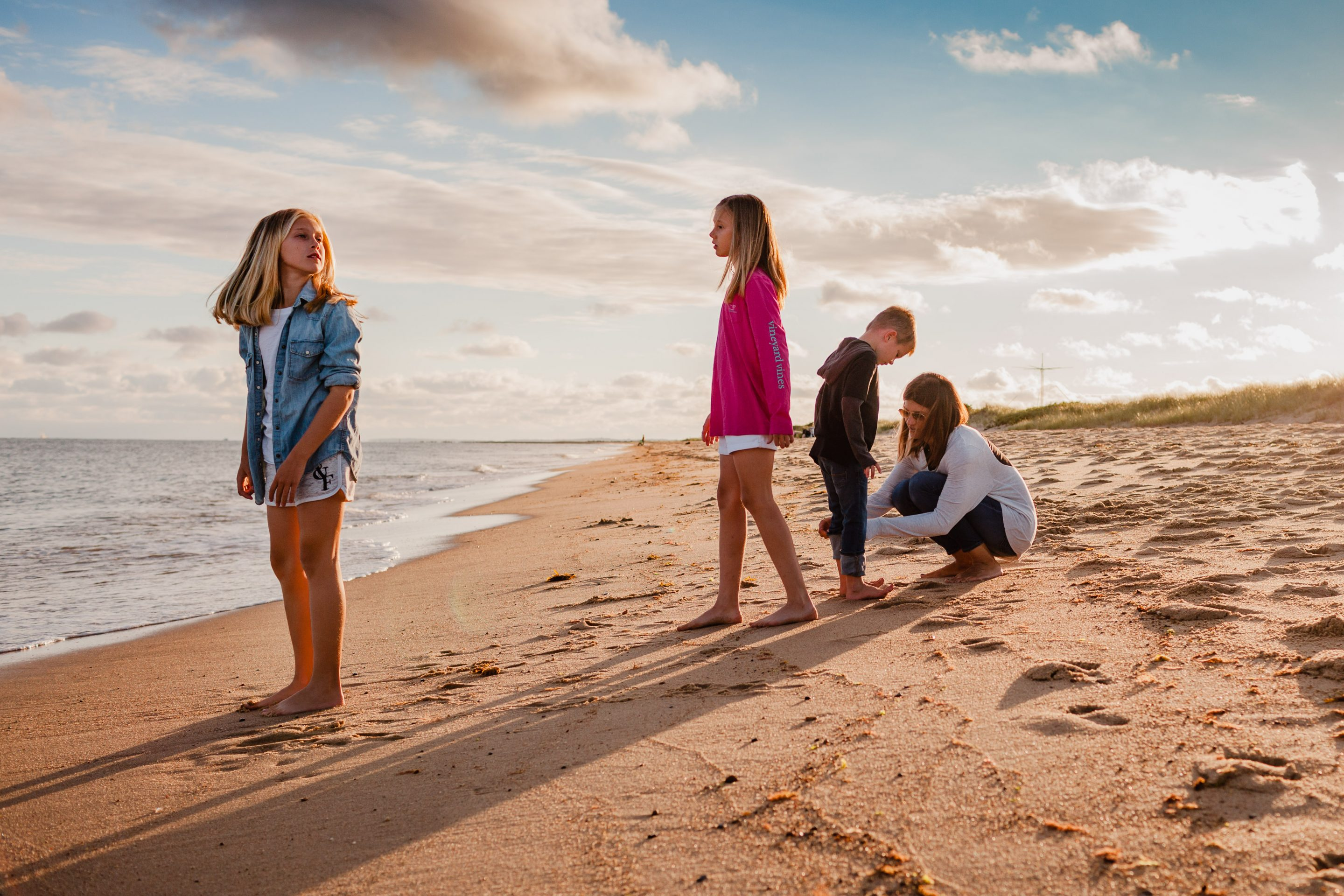 mom tying son's shoe at beach while daughters stand by ocean