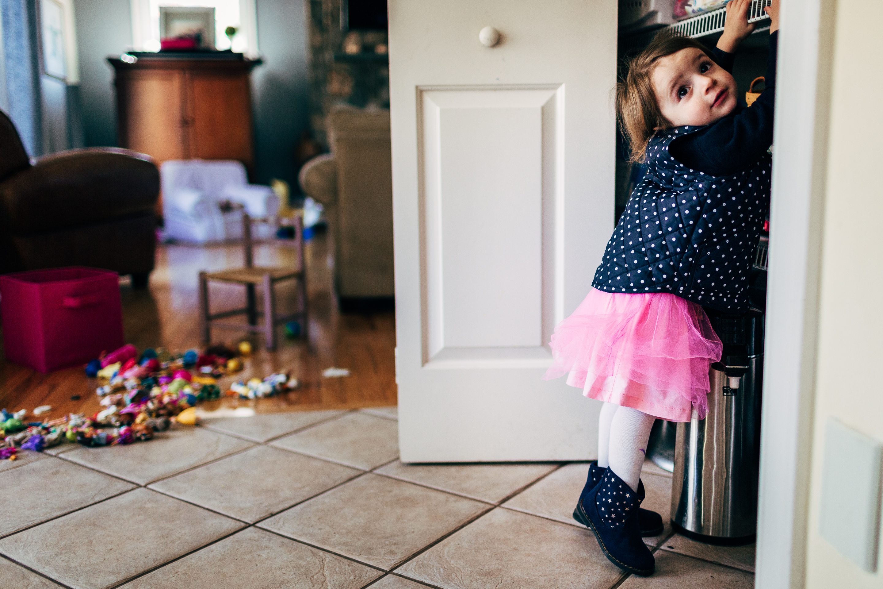 little girl in pink tutu and polka dot vest reaching into closet with mess in background