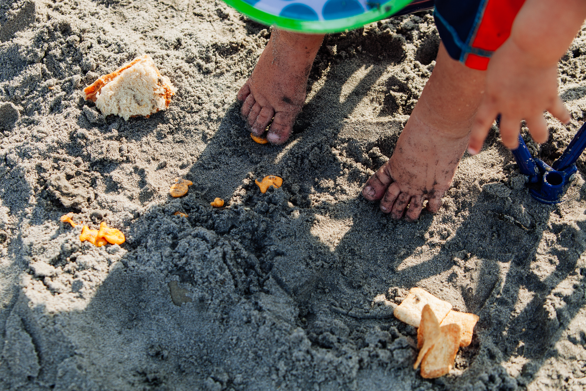 tiny toes in sand surrounded by spilled food