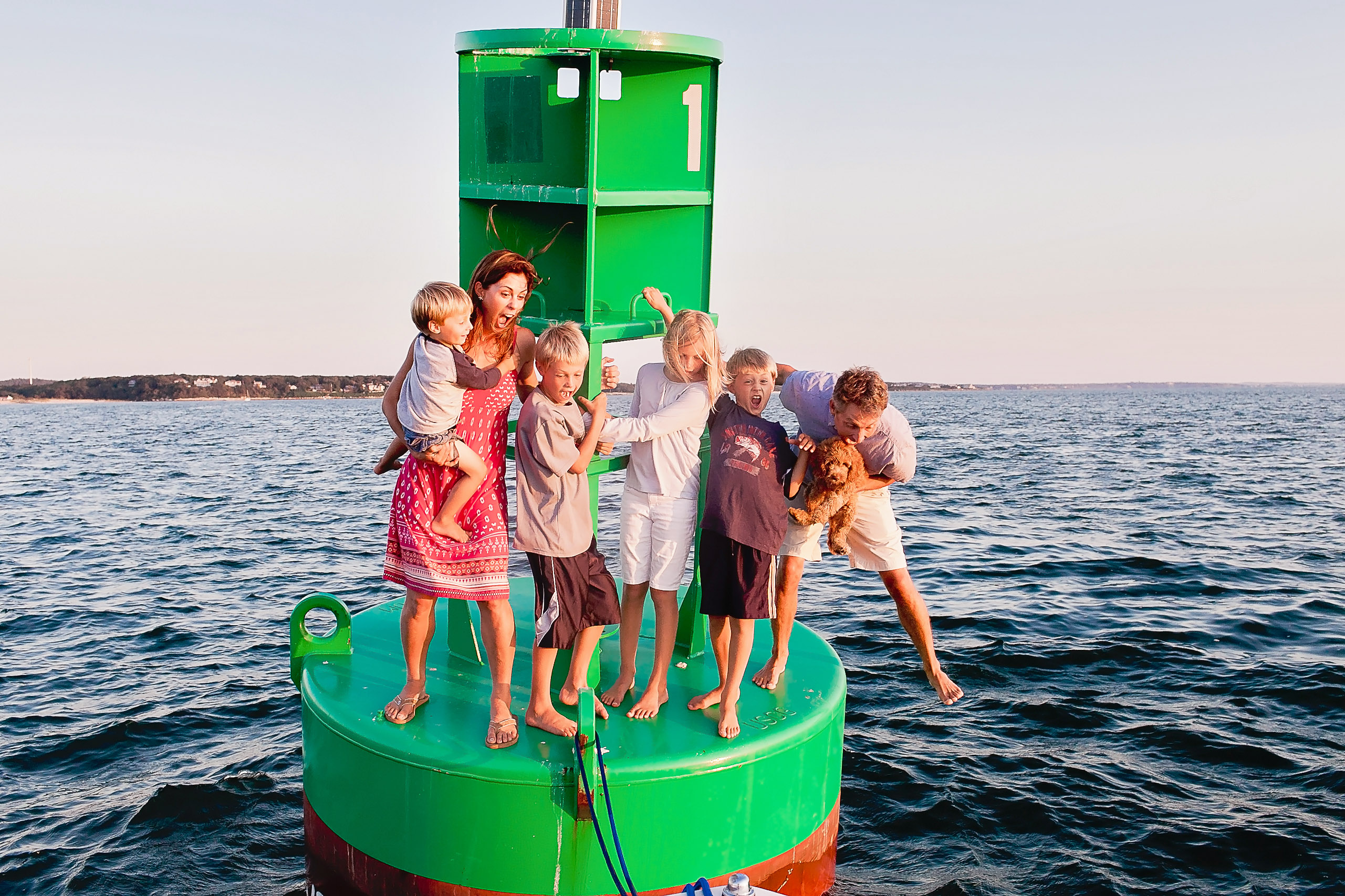 family standing on green buoy in middle of the ocean