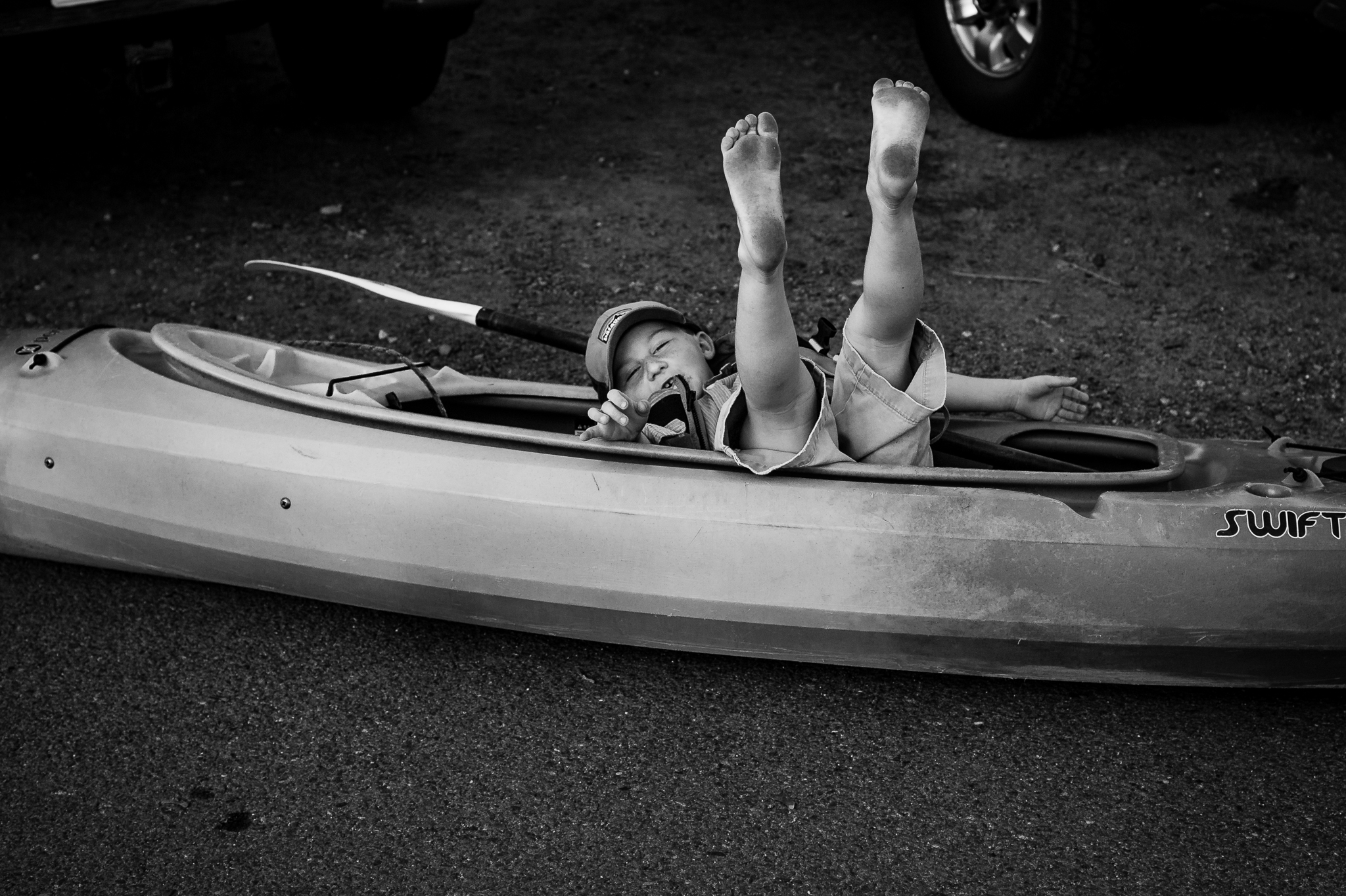 little boy falling backwards into a kayak with feet up