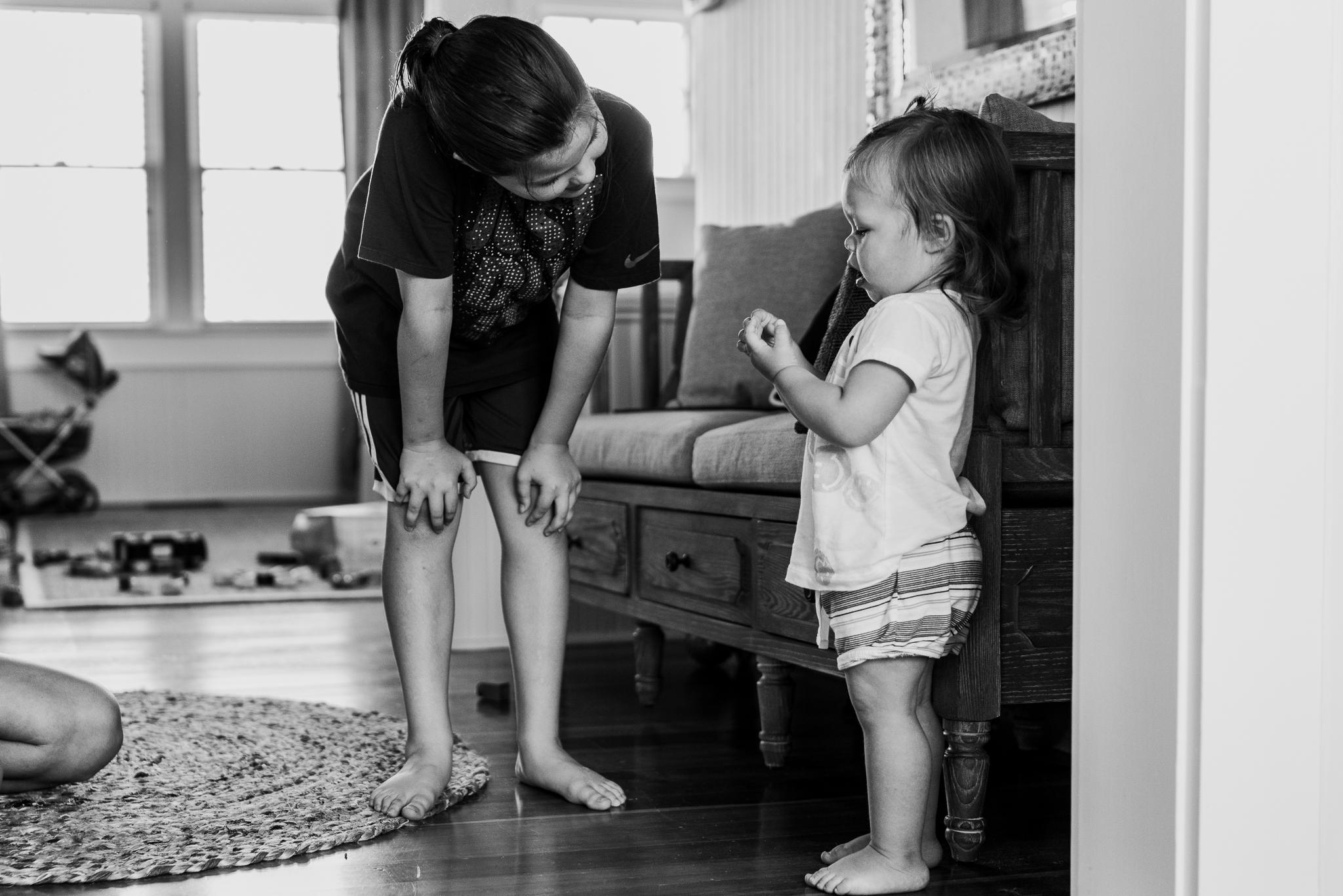 little girl bending to talk to toddler