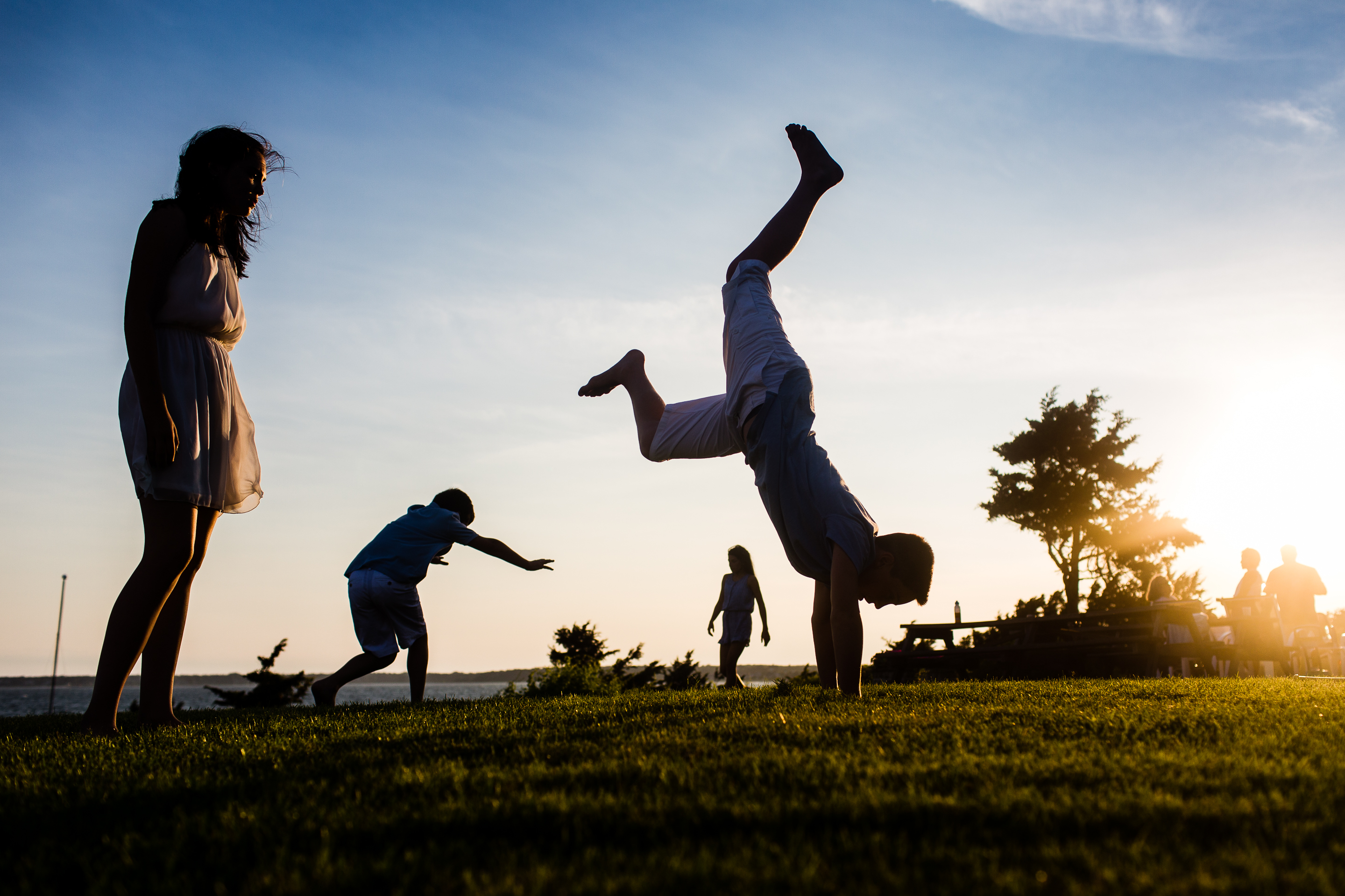 silhouette of kids doing cartwheels on grass