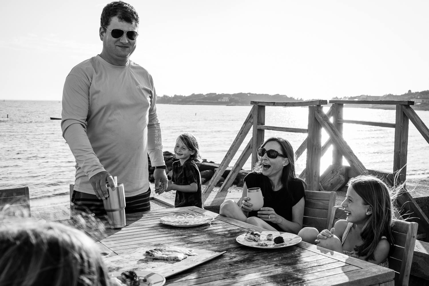 family laughing together eating outside by the ocean