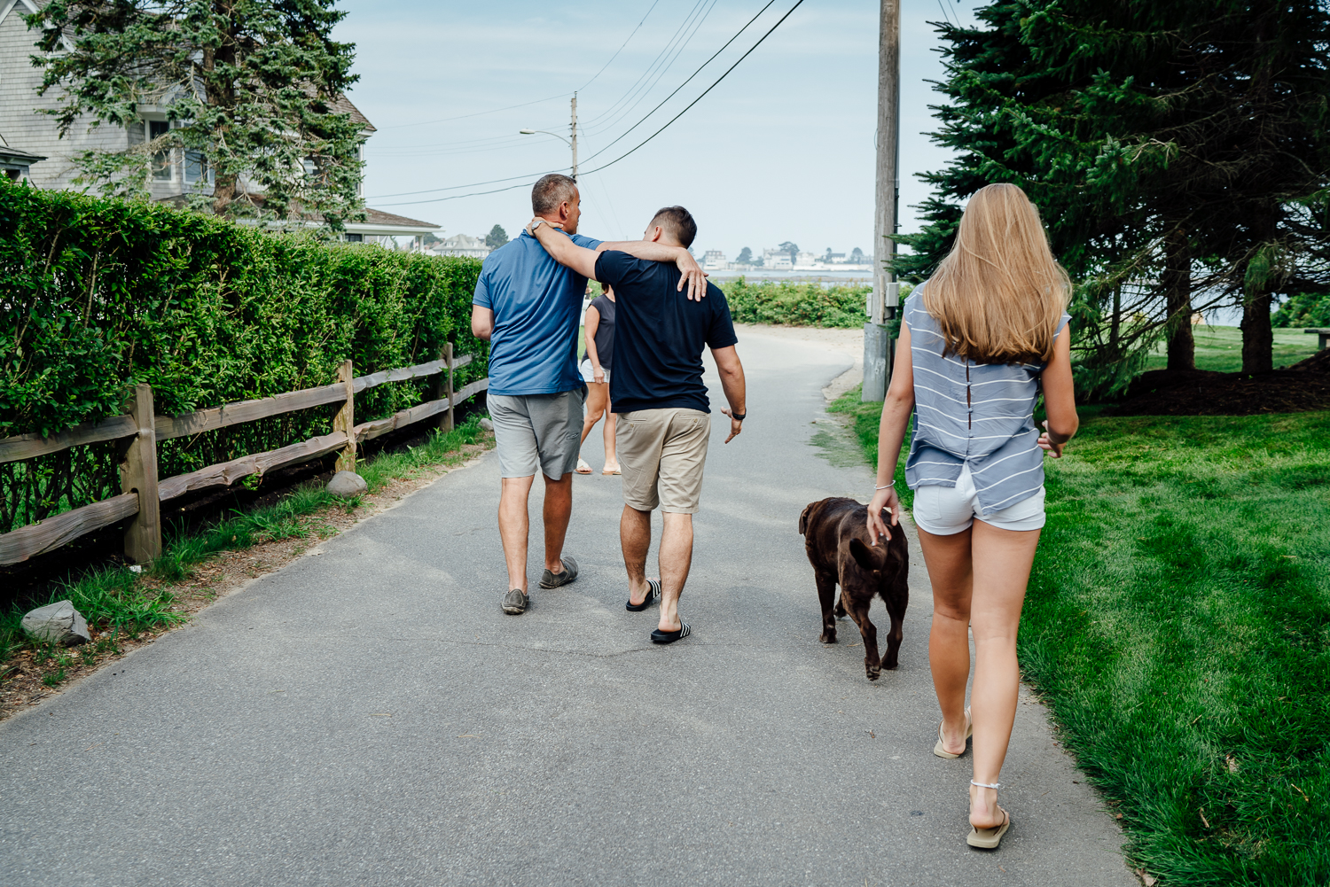 father and son walking with arms around each other while dog and daughter walk behind