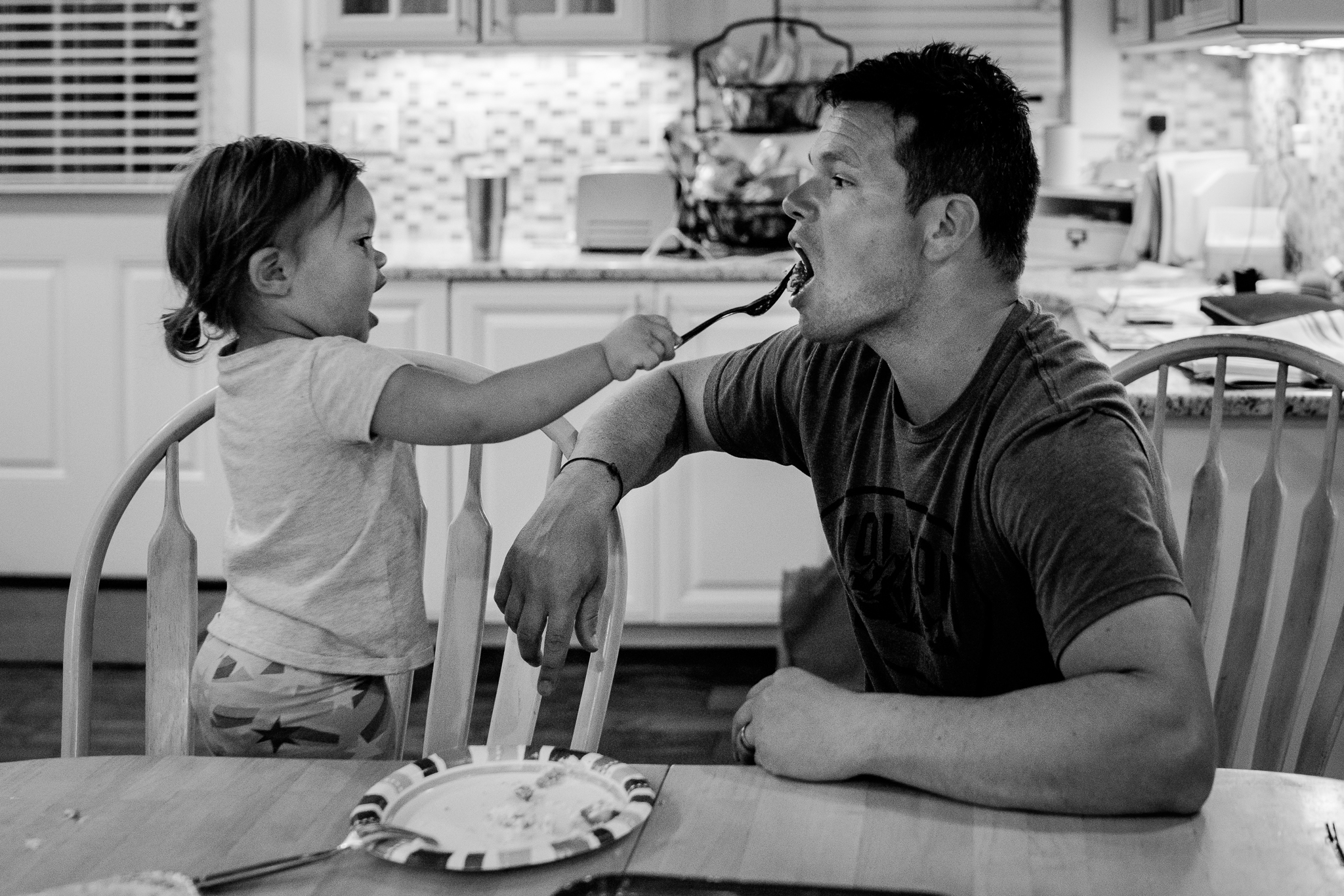 little girl feeding her father with a fork