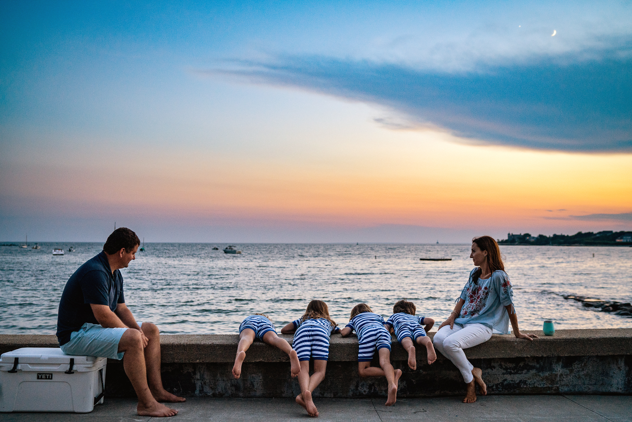 mom and dad sitting on beach wall at sunset with four kids in matching pajamas