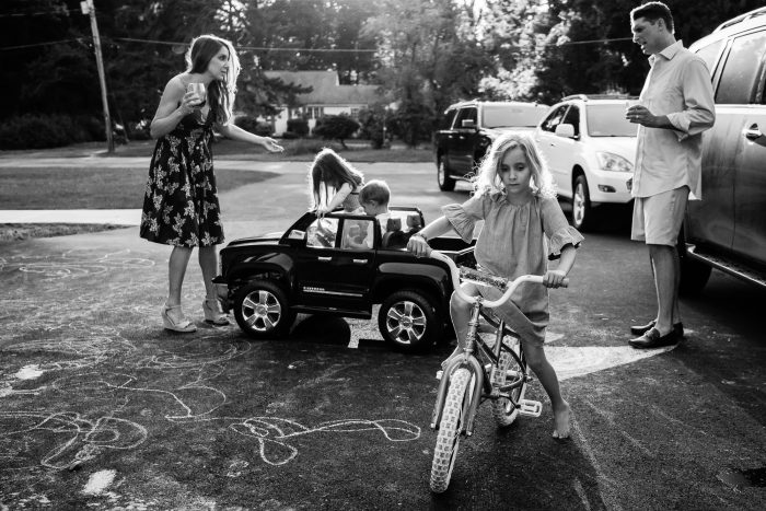 kids in toy car driving into mom holding cocktail and yelling at dad while family plays