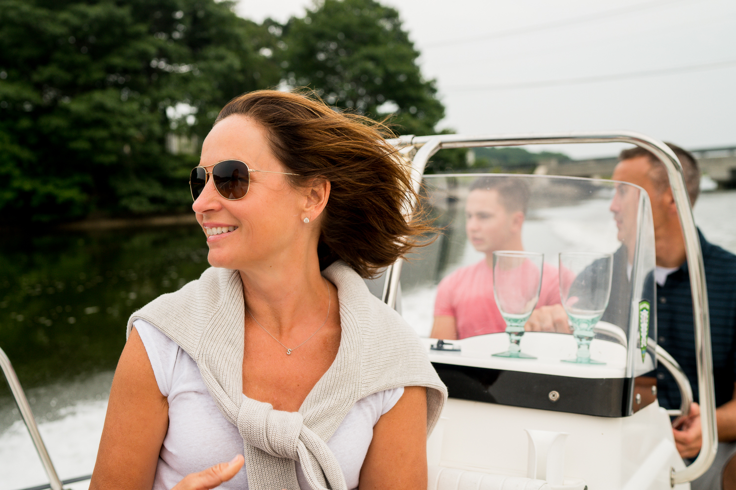 smiling woman on a boat with husband and son sitting behind her driving
