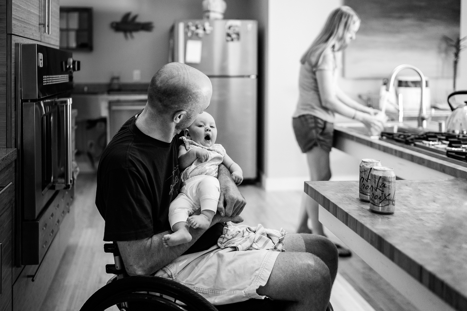 father in wheelchair holding yawning baby while mom washes dishes