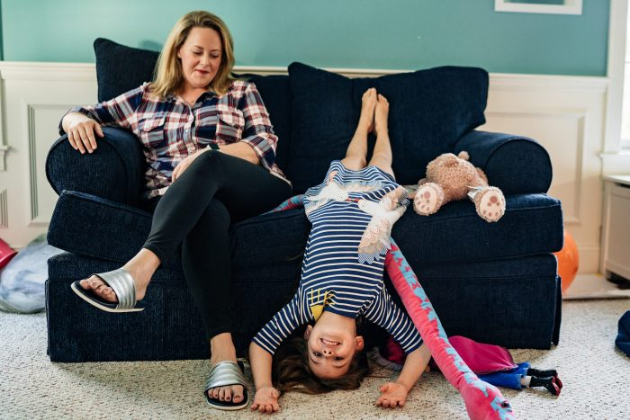 little girl sitting upside down on couch next to mom