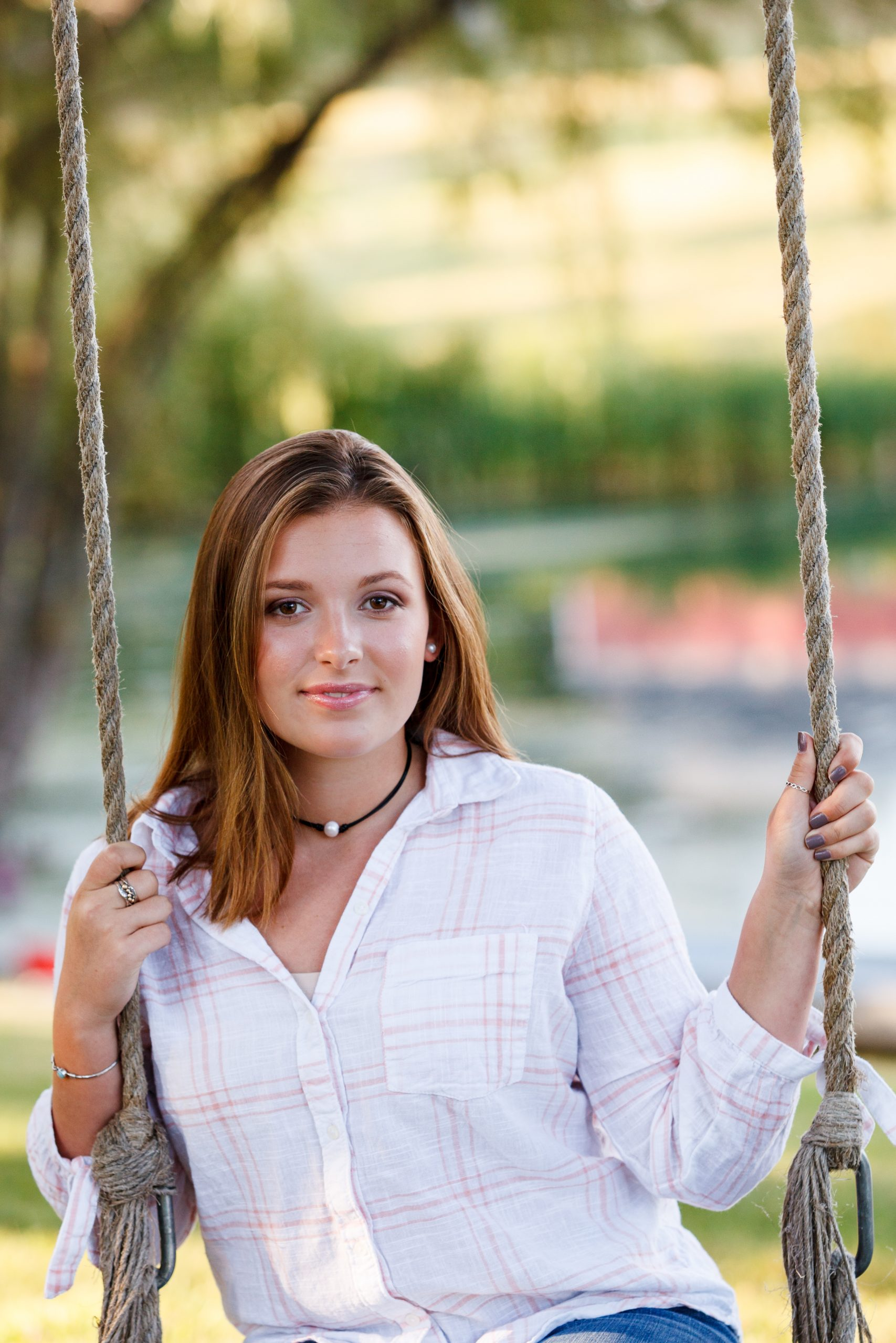 teenage girl in white button down shirt holding onto swing ropes