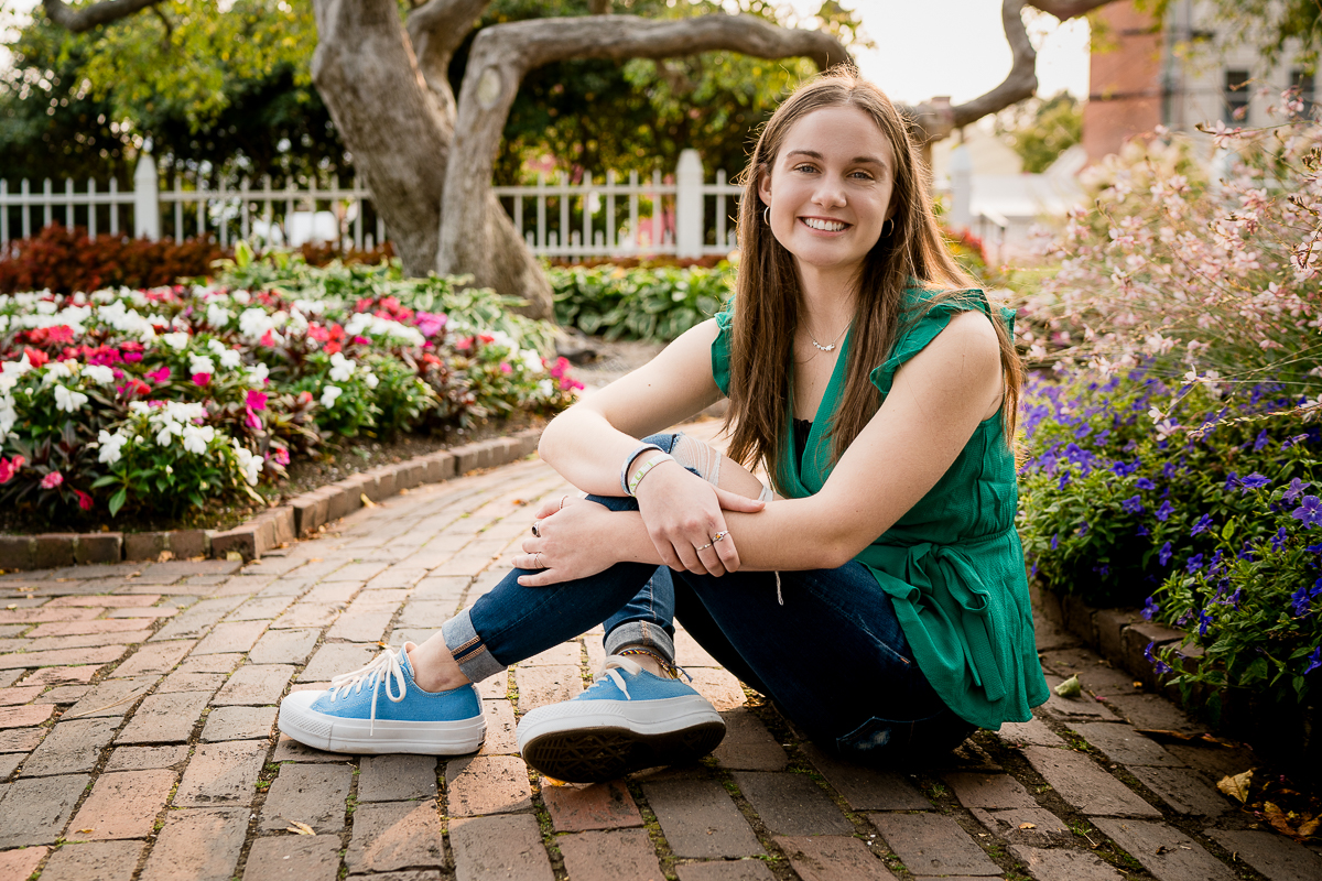 high school senior photo at prescott park nh girl wearing green shirt and jeans sitting by flowers