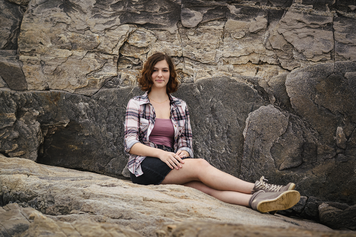 teenage girl wearing plaid shirt and black skirt sitting against large rock