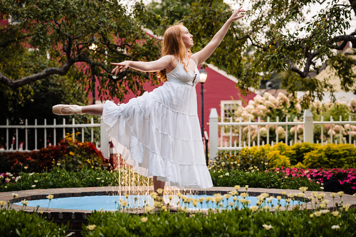 teenage girl wearing ballet slippers and white dress posing near fountain