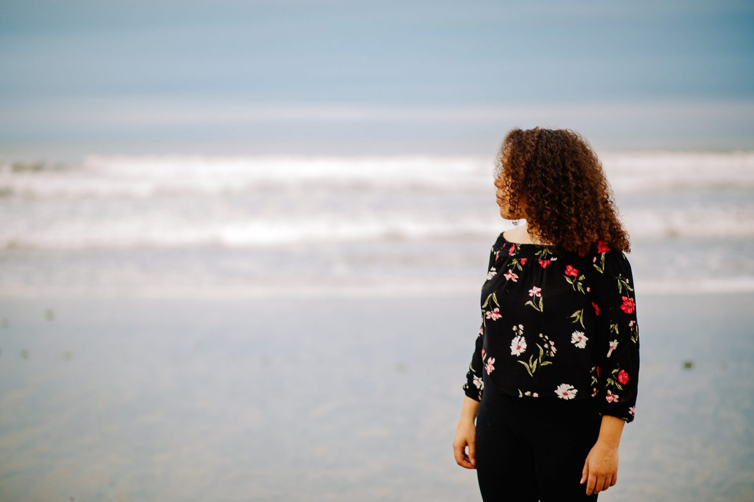 african american teenage girl at beach looking off to the side