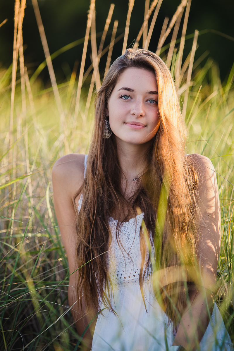 senior portrait of teenage girl sitting in beach grass wearing a white dress