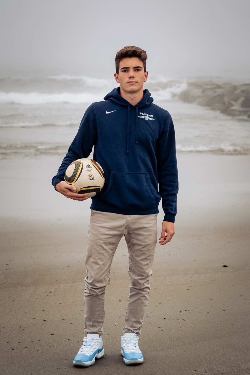 male senior in high school posing with soccer ball at beach in blue sweatshirt and khakis